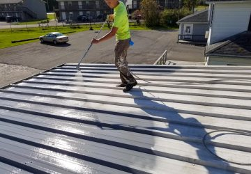 Man priming a metal roof
