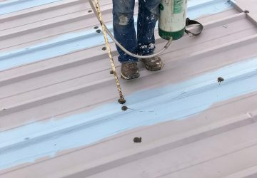 A Westmoreland roofing expert is sealing all fasteners with acrylic sealant.