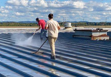 Men washing a metal roof